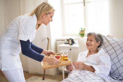 caregiver giving food to patient