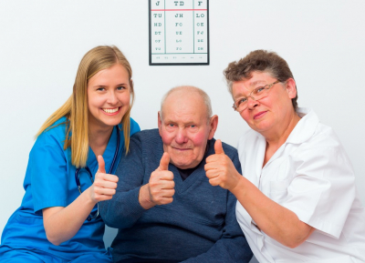 old man showing thumbs up with his caregivers